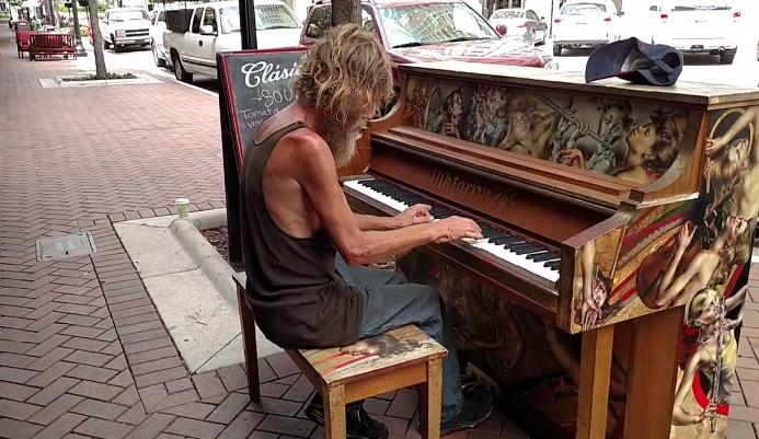 Người vô gia cư chơi đàn trên đường phố